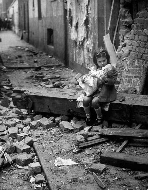Fetita engleză cu o papusa așezata pe ruinele caselelor distruse în bombardamentele. 1940.