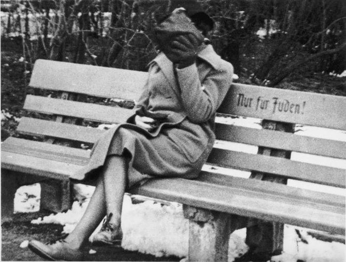 """O evreică din Austria stă pe banca, cu inscripția """"Numai pentru evrei."""""""